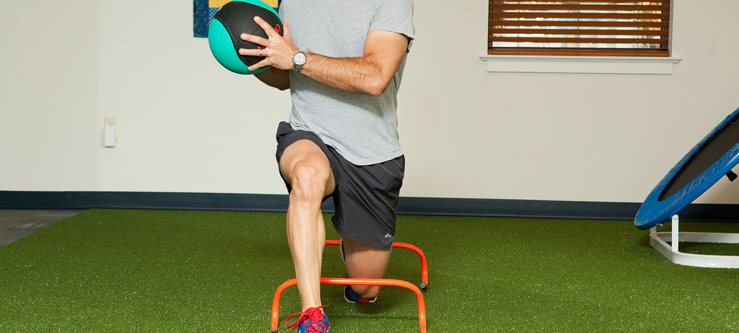 patient performing rehabilitation exercise with fitness ball